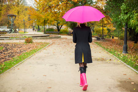 rainy day: Woman walking in park in autumn