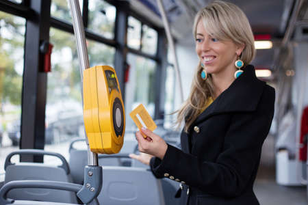 validating: Woman using electronic ticket punching machine in public transport