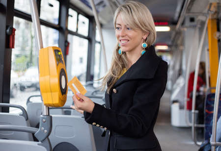 validating: Woman validating electronic ticket in public transport Stock Photo