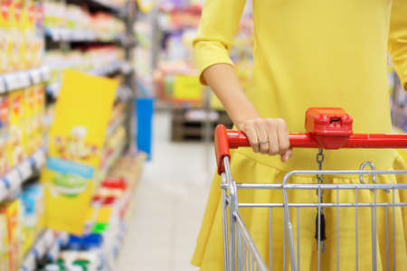 super market: Woman shopping for baby food in supermarket
