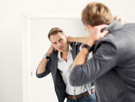 Casually dressed young handsome man in front of mirror