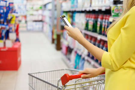 convenient store: Woman checking shopping list on her smartphone at supermarket