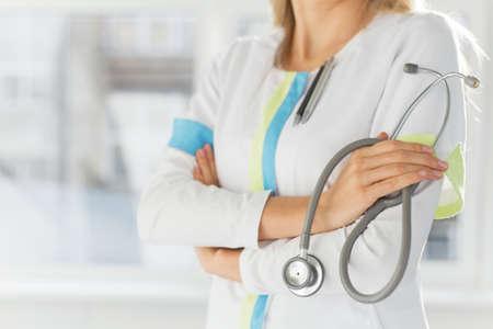 holding close: Female doctor holding stethoscope
