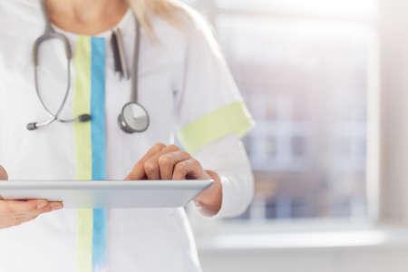 女性医師の病院でタブレット コンピューターを使用して