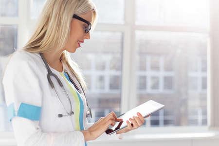 doctores: Doctora mirando los registros m�dicos sobre tablet PC
