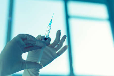 polio: Hands of the doctors filling a syringe