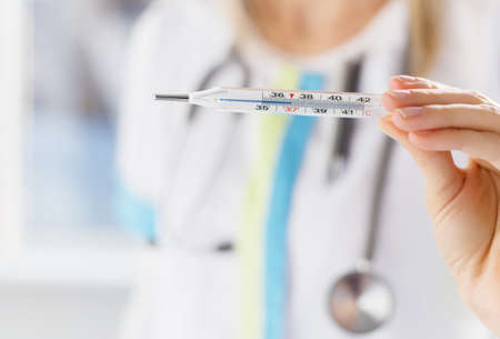 general practice: Doctor holding thermometer Stock Photo