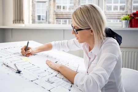 Young female architect working on blueprint Foto de archivo
