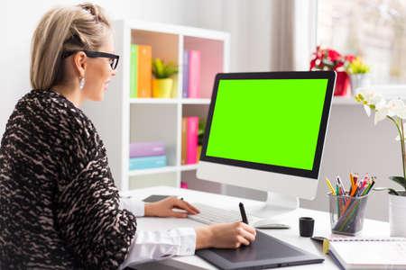 Diseñador usando tableta gráfica mientras se trabaja con el ordenador