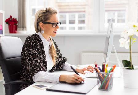 Jonge vrouwelijke ontwerper met grafisch tablet tijdens het werken met de computer Stockfoto