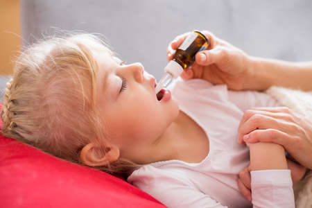 Parent giving medicine drops to her sick child Stock Photo