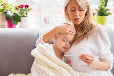 niños enfermos: Madre que controla la temperatura de su pequeña hija enferma