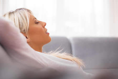 home audio: Relaxed woman listening to music on headphones at home