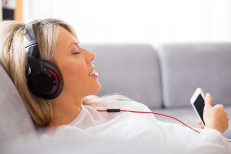 audifonos: Mujer Relaxed que escucha la m�sica en los auriculares en el hogar Foto de archivo