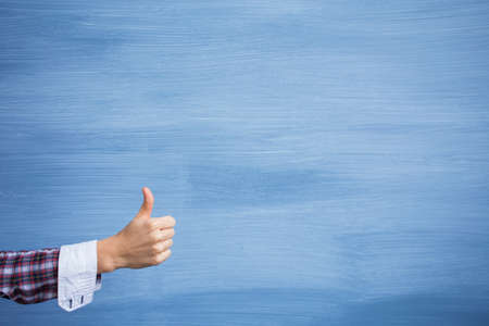 Hand showing thumbs up gesture on blue background Stockfoto