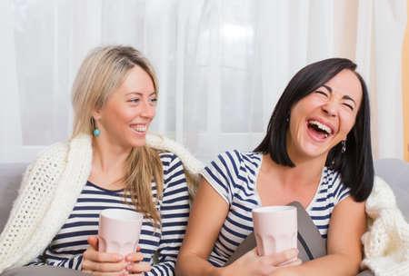 amigas conversando: Dos mujeres alegres riendo mientras est� sentado c�modamente en la cama Foto de archivo