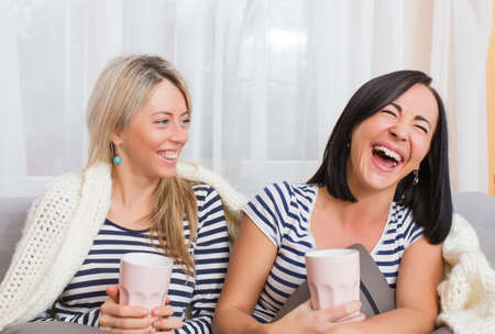 everyday people: Two cheerful women laughing while sitting comfortably in bed