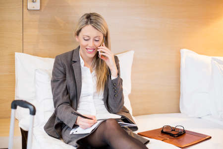 business woman phone: Business woman in hotel room talking on phone while on business travel Stock Photo