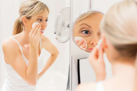 bathroom women: Young woman removing makeup in bathroom Stock Photo
