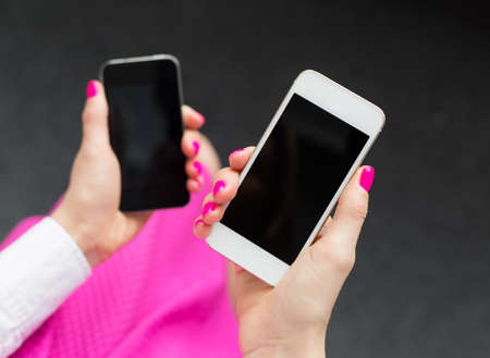 woman on phone: Woman holding two mobile phones Stock Photo