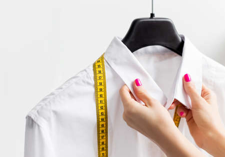 tailor measure: Woman tailoring business shirt Stock Photo