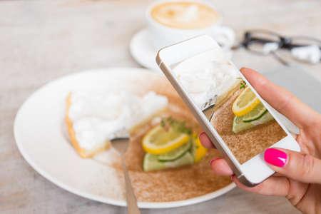 cafe internet: Mujer que toma foto de su pastel en el caf� con el tel�fono m�vil Foto de archivo
