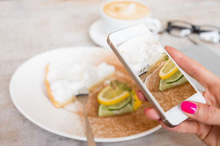 photo: Woman taking photo of her cake in cafe with mobile phone Stock Photo