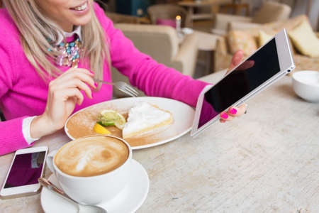 android tablet: Woman using tablet computer while having cake and coffee in cafe