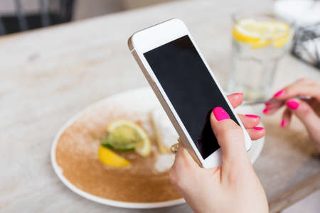 holding: Woman holding mobile phone in cafe