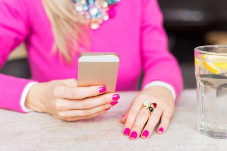 correo electronico: Mujer que usa el tel�fono m�vil en caf� Foto de archivo