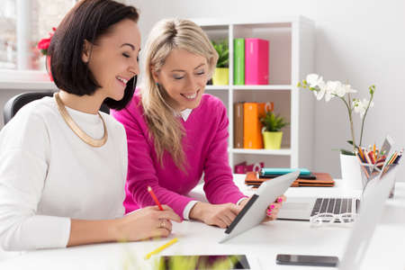 Two women looking at tablet computer while working in office