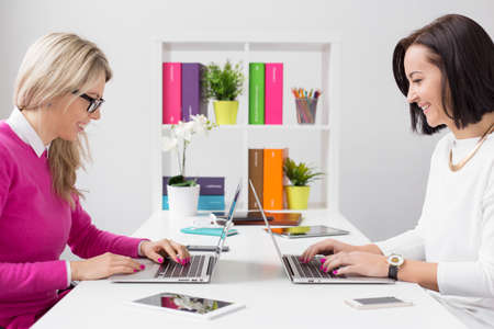 agencies: Two cheerful woman working with computers in the office Stock Photo