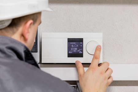 ingeniero: Ingeniero termostato de ajuste para el sistema de calefacci�n automatizado eficiente Foto de archivo