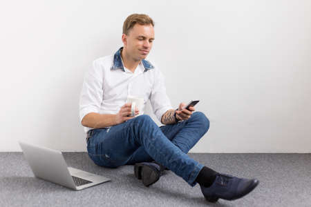 Relaxed young man sitting on floor and using mobile phone