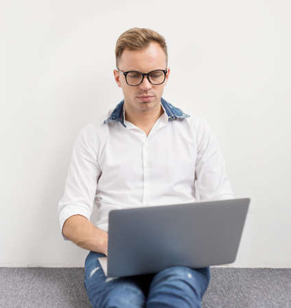 coder: Young hipster using laptop computer while sitting on floor.