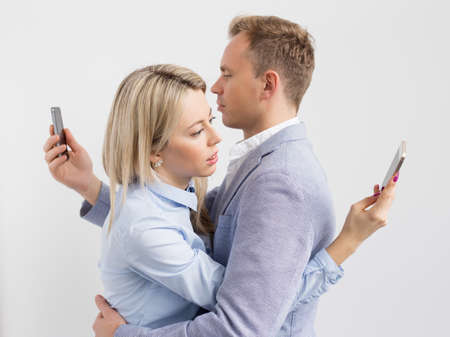 relationship problems: Young couple embracing and still using their mobile phones Stock Photo