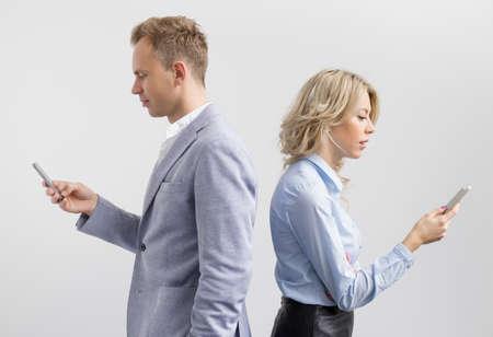 malos habitos: Dos personas demasiado ocupados con sus teléfonos móviles