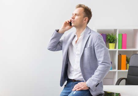 casually: Casually dressed young businessman talking on phone in office