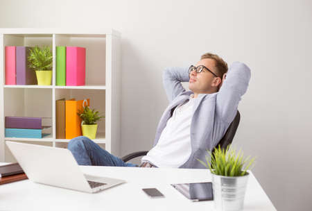 easy chair: Relaxed businessman sitting in chair with hands behind head Stock Photo