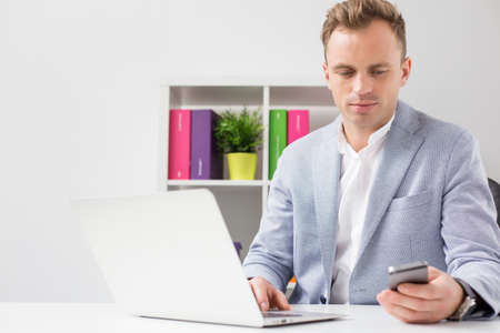 data synchronization: Young businessman in office Stock Photo