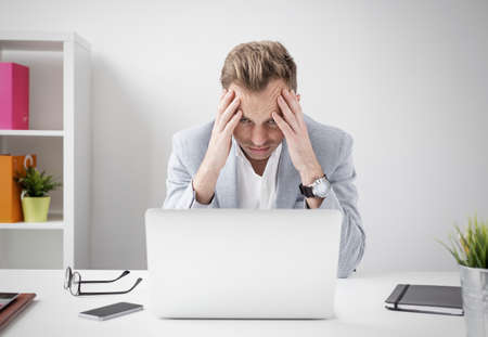 headache: Depressed businessman sitting at computer