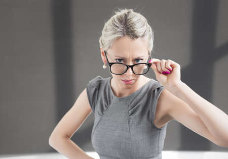strict: Strict teacher looking through glasses with serious expression Stock Photo