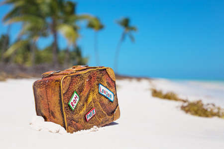 Travel suitcase toy on the beach photo