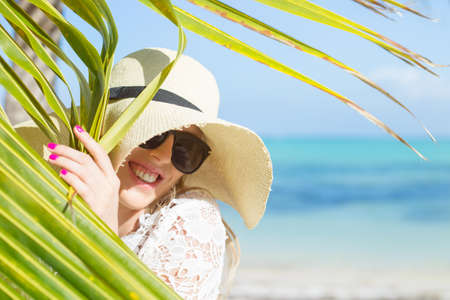 Woman with summer hat on the beach hiding behind palm leaf