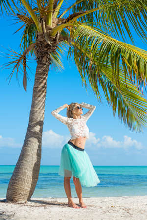 under tree: Young happy woman standing on beach under palm tree