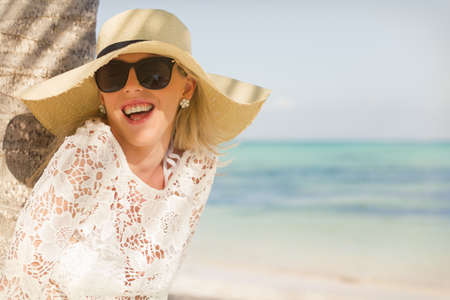 Cheerful woman laughing under the palm tree at the beach