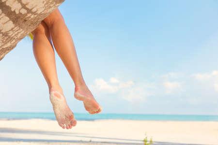 piedi nudi di bambine: Donna che si siede sulla palma in spiaggia tropicale