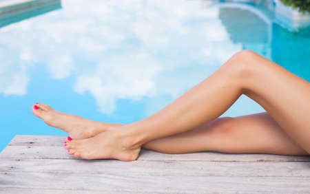 pool deck: Beautiful slim women legs by the swimming pool Stock Photo