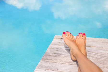 Bare woman feet by the swimming pool