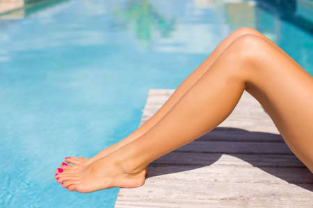 pedicure: Beautiful tanned women legs by the swimming pool Stock Photo